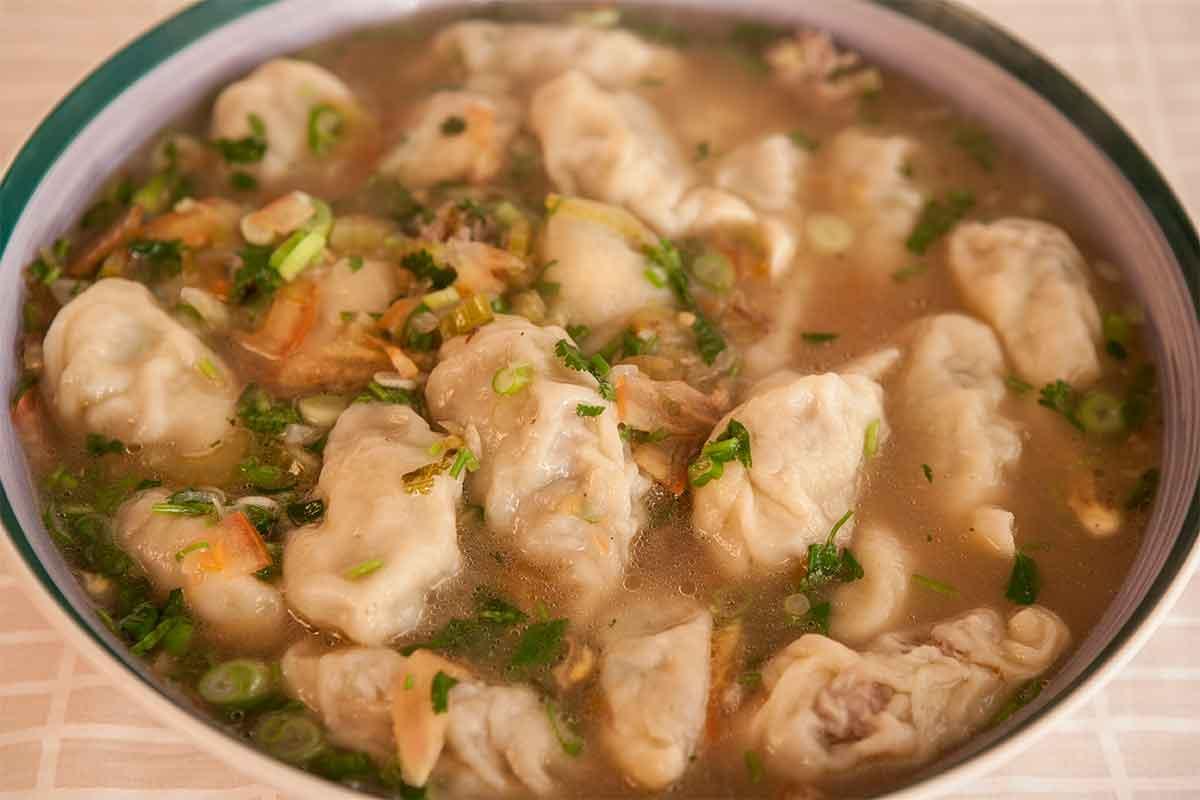 """Tsi tsi momo shape in """"shamey mothuk,"""" veggie dumpling soup."""