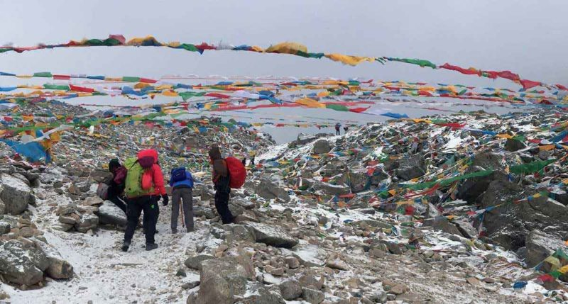 Mount Kailash: At the highest point on the Kailash trek — the 18,500 ft Dolma La Pass — a young Chinese woman, in blue, bent over, in trouble from altitude sickness.