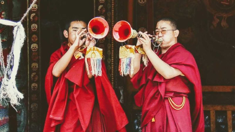Monks blowing horns at Nechung Monastery near Lhasa