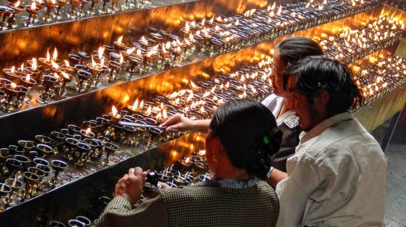 Tibetans lighting butter lamps at the base of the Chakpori in Lhasa